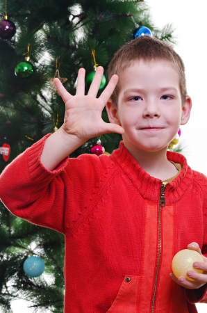 five years old: Young boy showing five fingers in front of christmas tree, looking at camera, vertical shot