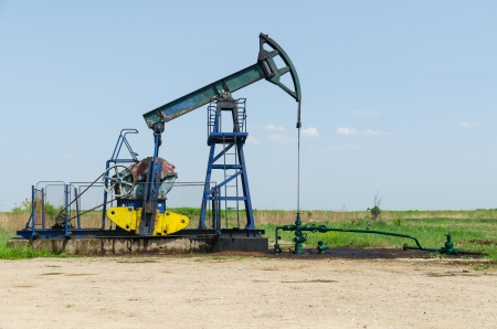 jack pump: Oil Well Machine in Field on Clear Sunny Day, horizontal shot