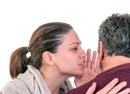 Young woman side portrait speaking in the ear of mature man showing from behind, horizontal shot over white photo