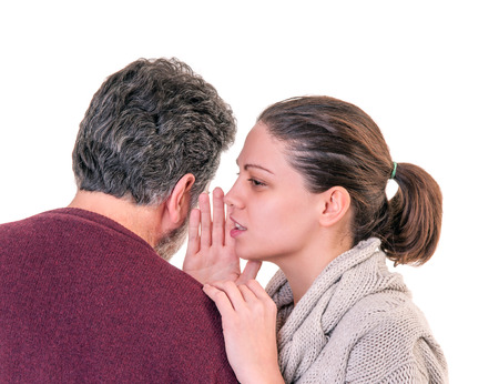 stupor: Young woman side portrait speaking in the ear of mature man showing from behind, horizontal shot over white
