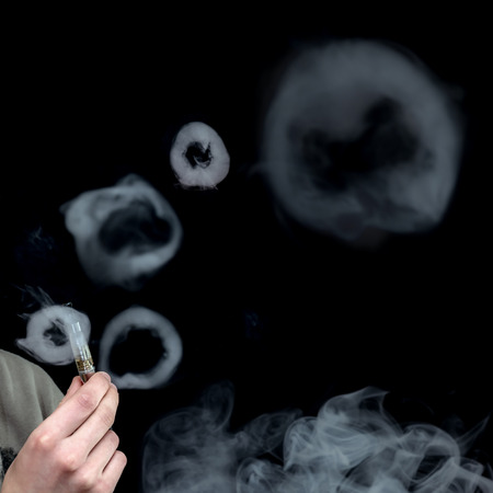 background e cigarette: Electronic Cigarette Smoke in Circles over Black Background, Selective focus on hand holding e-cigarette