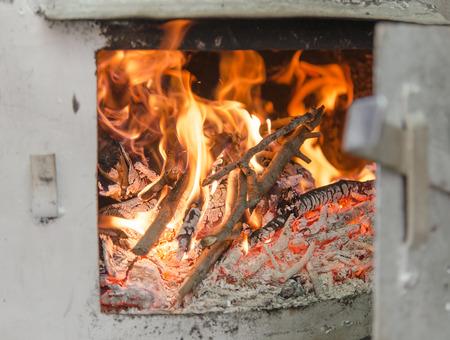 distillation: Destilaci�n todav�a c�mara Pot chimenea quema de ramas de madera con la puerta abierta, detalle con el enfoque selectivo