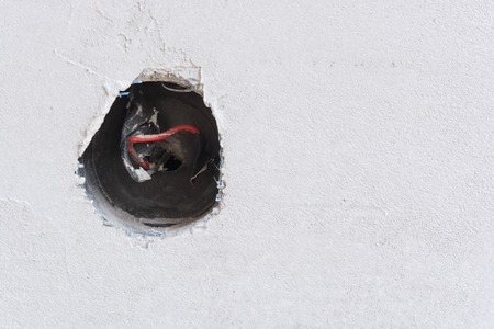 plastered wall: Plastered wall with exposed wires in wall socket