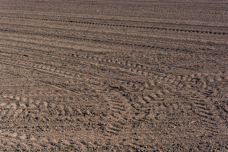 fertile land: Plowed  fertile soil with tractor traces - cultivated land Stock Photo