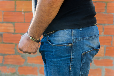 confiscation: Arrest, close-up shot mans hands with handcuffs in front of terracotta brick blocks wall, left hand side