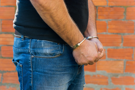 sequestration: Arrest, close-up shot mans hands with handcuffs in front of terracotta brick blocks wall, right hand side Stock Photo