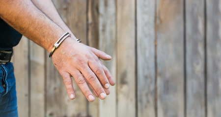 confiscation: Arrest, close-up shot mans hands with handcuffs in front of plank wood  wall with copy-space