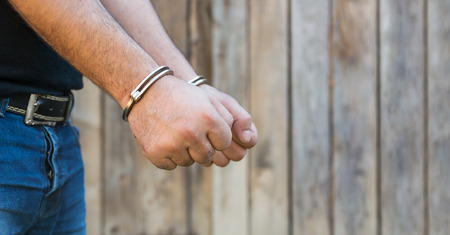 Arrest, close-up shot mans hands with handcuffs in front of plank wood wall with copy-space Stock Photo