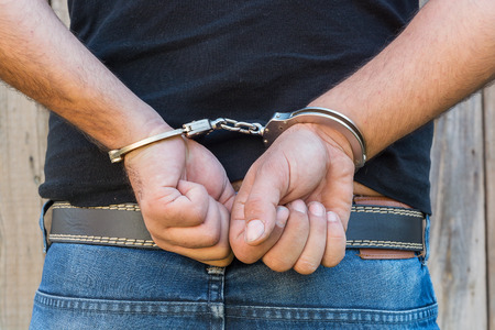 confiscation: Arrest, close-up shot mans hands with handcuffs in front of plank wood wall