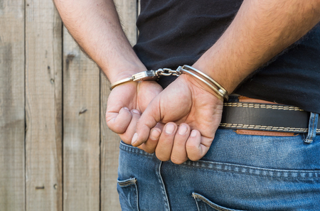 confiscation: Arrest, close-up shot mans hands with handcuffs in front of plank wood wall with copy-space Stock Photo