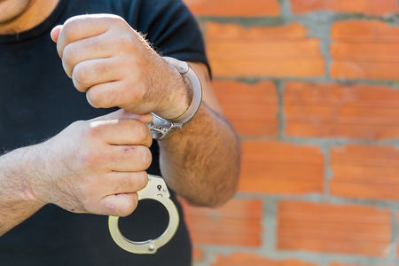 sequestration: Arrest, close-up shot mans hands unlocking handcuffs in front of terracotta brick blocks wall with copy-space