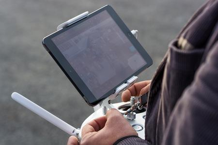 snoop: Zrenjanin, SERBIA: October 29, 2015, detail of man flying Dji Inspire 1 remote controller with Ipad displaying camera frame on AVIV park opening