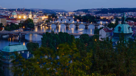 A beautiful view of Prague's bridges at dusk with lights on