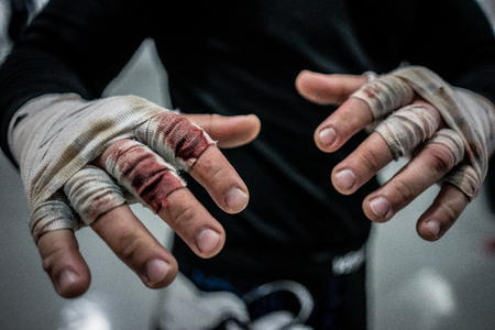Close up on bloody wrapped hands after fight