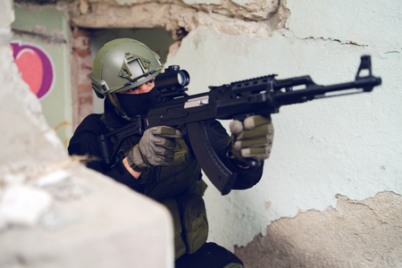 military or police special forces soldier private contractor armed force assault rifle attack aiming in the building war operation anti terrorist
