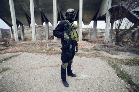 Armed special forces soldier terrorist in dark uniform and helmet standing in front of ruined building