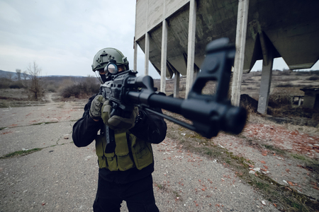 Special Forces soldier SWAT in helmet with rifle aiming in front of the devastated building