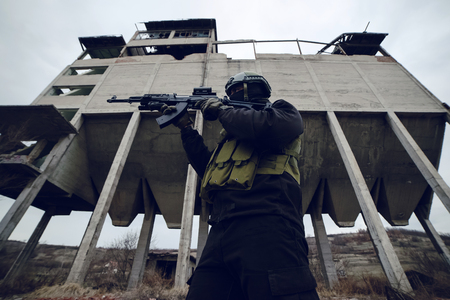 Armed special forces soldier terrorist in dark uniform and helmet standing in front of ruined building aiming shooting gun fire Stock Photo