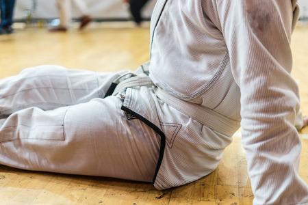 Brazilian Jiu JItsu Judo BJJ fighter white belt resting after first fight at the tournament