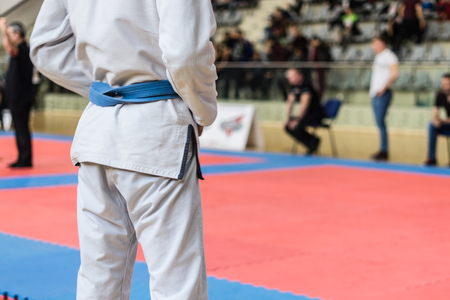 Close up on midsection of judo BJJ fighter holding his blue belt while waiting to compete at the tournament