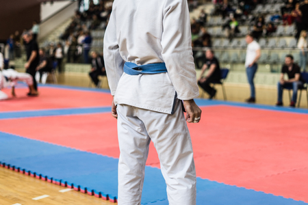 Midsection of Brazilian Jiu JItsu BJJ fighter blue belt while waiting to compete by tatami at the tournament