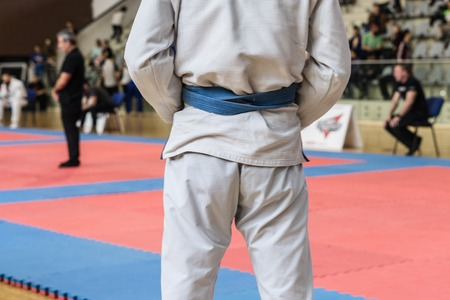 Close up on midsection of brazilian jiu jitsu BJJ fighter holding his belt while waiting to compete at the tournament 版權商用圖片