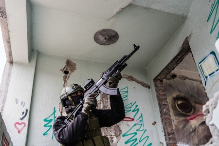 Young Special forces SWAT soldier aiming with assault rifle gun at the ruined building war terrorist battle zone airsoft