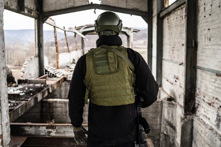 Special forces modern soldier standing in ruined building after the intervention war battle