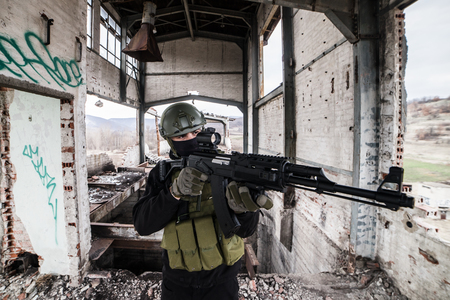 Special military soldier police at the battle zone terrorist on the stairs of the building aiming the assault rifle gun drill airsoft 스톡 콘텐츠