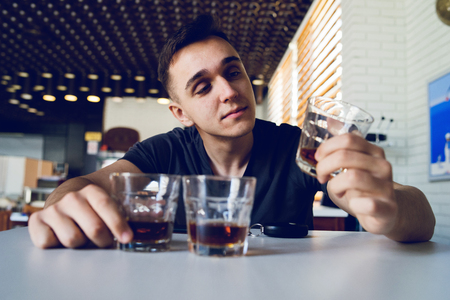 Young man drunk at pub holding glass of alcohol whiskey brandy