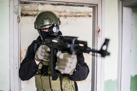 Anti terrorist SWAT special police in action aiming automatic rifle on the rescue mission Stock Photo