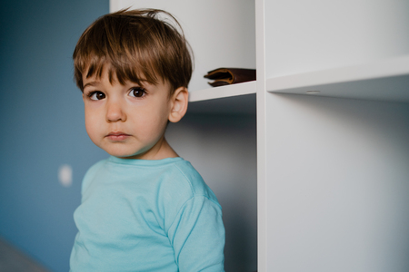 Portrait of a little boy in blue at home standing by the wall