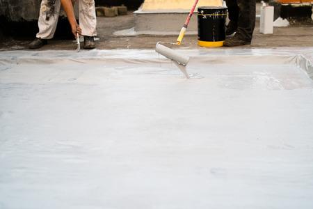 Dachisolierung, zwei Mann beim Auftragen von Material mit der Farbrolle und dem Pinsel zur Isolierung des Gebäudes Standard-Bild