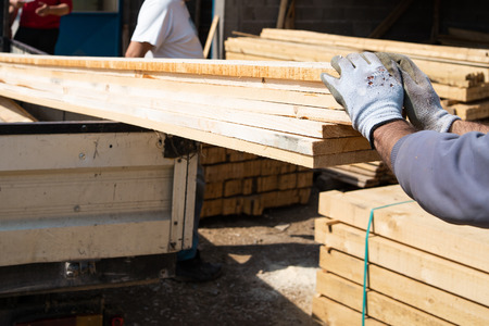 Workers holding material planks by the truck ready to delivery to the construction site loading