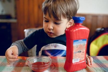 Petit garçon mangeant des pommes de terre frites frites avec du ketchup par la table à la maison