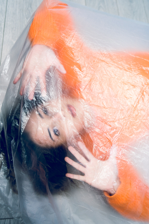 Young woman wrapped in nylon transparent bag trapped frustrated freedom human trafficking concept