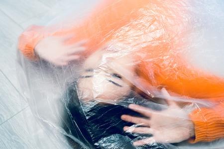 Junge Frau, die in eine durchsichtige Nylontasche gehüllt ist, gefangen frustriertes Freiheitskonzept des Menschenhandels