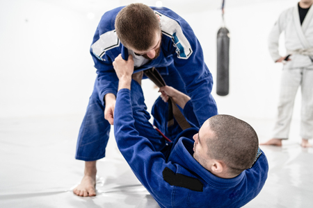 Two young BJJ Brazilian Jiu jitsu Athlete fighters training sparing technique at the academy fight