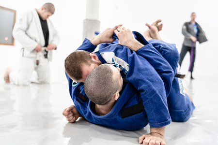 Two young BJJ Brazilian Jiu jitsu Athlete fighters training sparing technique at the academy fight lapel gi kimono