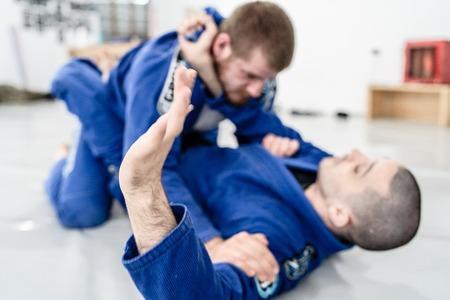 Deux jeunes combattants d'athlète de Jiu Jitsu brésilien BJJ s'entraînant à la technique d'épargne au combat de l'académie Banque d'images