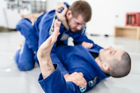 Zwei junge BJJ brasilianische Jiu-Jitsu-Athleten, die beim Akademiekampf sparsame Technik trainieren technique Standard-Bild