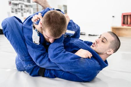 Zwei junge BJJ brasilianische Jiu-Jitsu-Athleten-Kämpfer trainieren sparsame Technik an der Akademie kämpfen gegen Choke