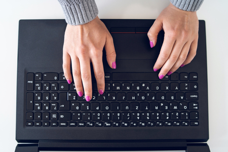 High angle view on womans hands woman using laptop on the white table typing on the black keyboard