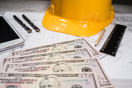 Construction industry costs money us dollars banknotes by tools safety equipment and blueprints Banco de Imagens - 121647967