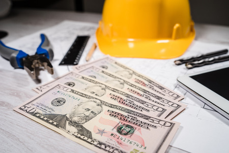 Construction industry costs money us dollars banknotes by tools safety equipment and blueprints