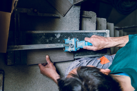 Close up on construction worker craftsman using tool for cutting ceramic tiles for laying installation to the bathroom Zdjęcie Seryjne