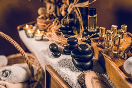 Spa essential aromatic oil in vintage bottle and massage basalt zen stones and candles on the table 스톡 콘텐츠