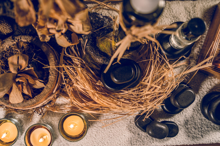 Spa essential aromatic oil in vintage bottle and massage basalt zen stones and candles on the table Stok Fotoğraf - 122296452