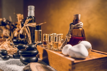 Spa essential aromatic oil in vintage bottle and massage basalt zen stones and candles on the table Imagens