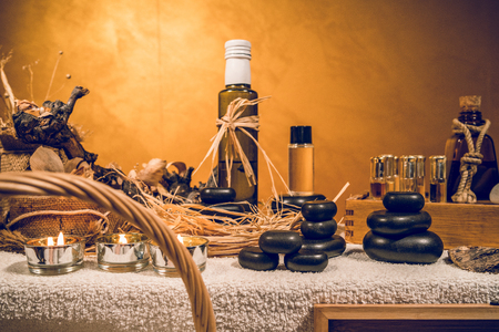 Spa essential aromatic oil in vintage bottle and massage basalt zen stones and candles on the table Banque d'images